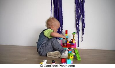 Kid playing with colored blocks of constructor on wooden floor. Gimbal motion