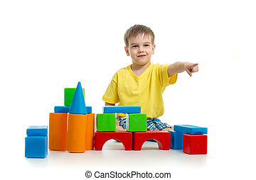kid playing with colorful building blocks and pointing direction by finger