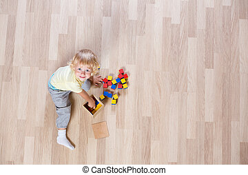 Kid playing with colorful toys on floor top view