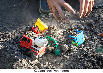 Kid playing with Plastic Toy Tractors in yard