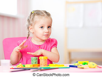 kid playing with play clay at home or  playschool