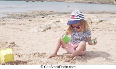 Kid playing with sand. Little girl plays on the beach