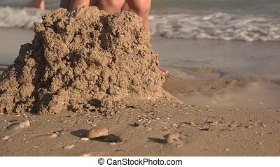 Kid playing with sand, slow-mo. Boy on seashore.