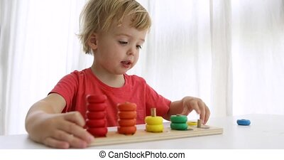 Kid playing with wooden developing puzzle toys. Educational...