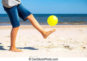 Kid playing with yellow beach ball on the sand by the sea water on a sunny day. Copy space for text. Vacation background.