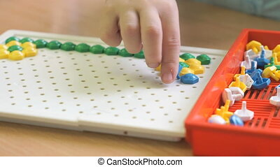 Kid plays a intellectual game at a table - Kid plays a...