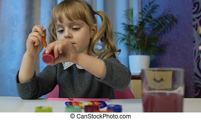 Cute little girl child sitting and painting on paper. Kid pupil artist drawing coloring picture rainbow with paints during quarantine coronavirus lockdown at home. Enjoying hobby, children development