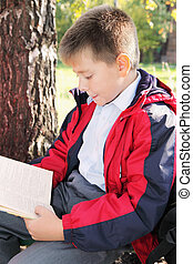 Kid reading book in park sideview
