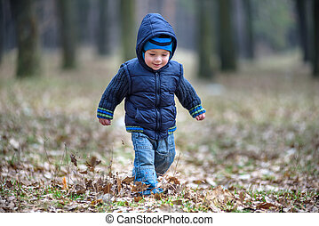 kid running in the outumn forest. Boy happy  in fallen leaves to his mother