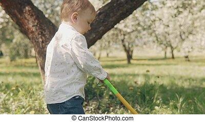 Kid runs on green grass. Little boy takes first step on fresh grass in city park