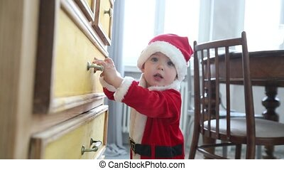 Kid Santa suit trying open chest drawer wardrobe