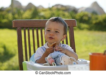 Kid sat eating in high chair
