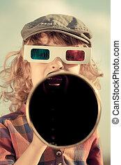 Kid shouting through vintage megaphone. Cinema concept. Retro style