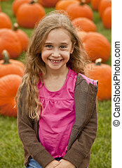Kid Sitting In A Pumpkin Patch