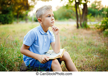 Kid sitting in the forest with book on the knees and looking awa