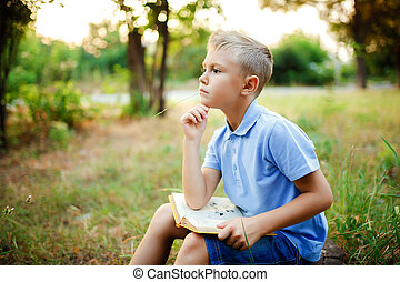 Kid sitting in the forest with book on the knees and looking away.