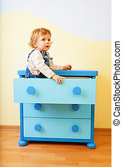 Kid sitting inside cabinet box