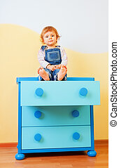 Kid sitting on the cabinet
