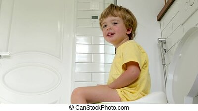 Kid sitting on toilet in bathroom at home - Cute toddler boy...
