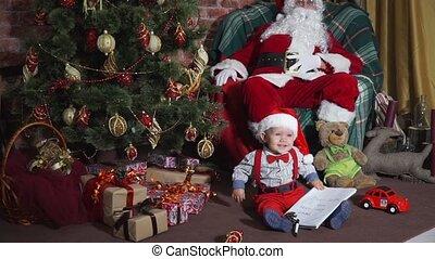 Kid sitting under a tree near the Santa in chair