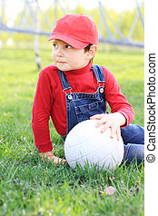 Kid sitting with ball