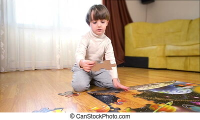 Kid solving a puzzle - Kid solving a floor puzzle at home