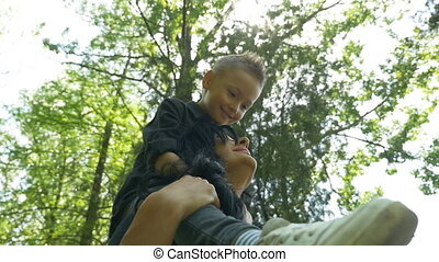 Kid standing on mother shoulders while the two are spinning around in the forest