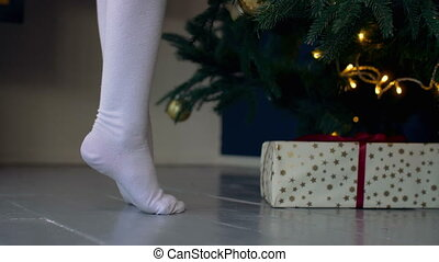Kid standing on tiptoes near Christmas tree - Low section of...