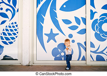 Kid stands against the background of blue flowers painted on a white wall