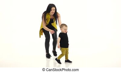 Kid steps on the floor in a spacious room. White background....