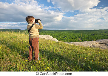Kid take a photography. Child photographs nature in mountain.