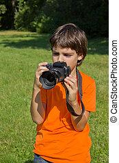 boy taking shots with photocamera in garden