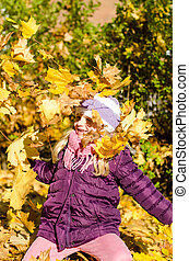 kid throwing autumn leaves