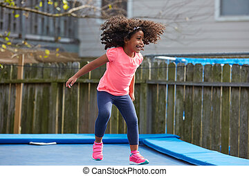 Kid toddler girl jumping on a trampoline