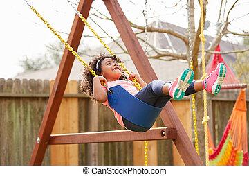 Kid toddler girl swinging on a playground swing