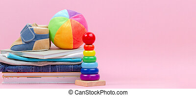 Kid toys, books and clothes on pink background