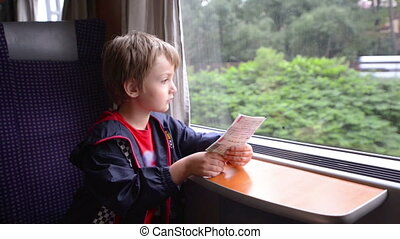 Kid Traveling by Train - Cute boy traveling by train looking...