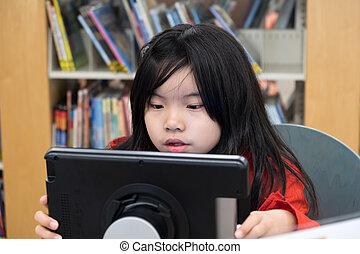 Kid using digital tablet in library