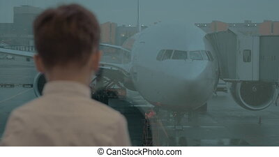 Kid waiting at airport and looking at plane through the window