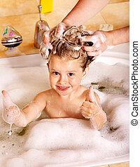 Child washing hair in bubble bath.