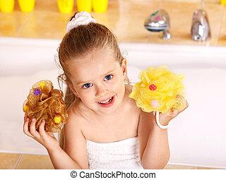 Kid washing in bath.
