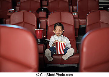 Kid watching movie in an empty cinema - Wide view of a...