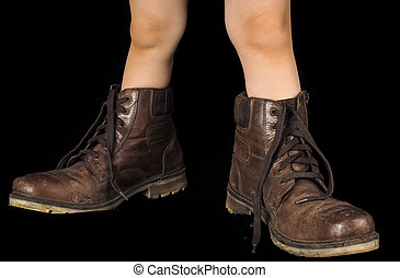 Kid wearing a pair of too big untied and unpolished brown leather boots, on black