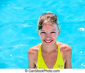Kid wearing yellow bikini in swimming pool.