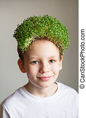 Kid with a microgreens hair. Healthy vegan foods concept. ...