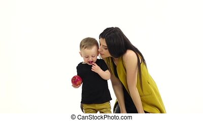 Kid with an apple in his hands, runs away from his mother. White background. Slow motion