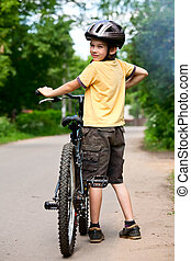 Young boy standing with bicycle, shallow dof