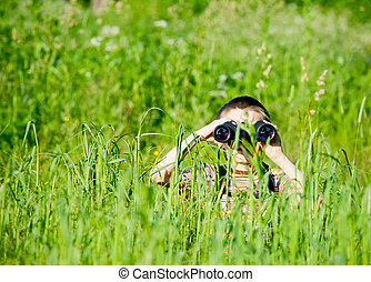 Kid with binocular - Young boy in a field looking through ...