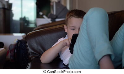 Kid with digital tablet relaxing in airport lounge