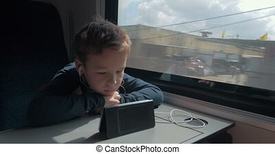 Kid with earphones watching cartoon on cell in train - Boy...